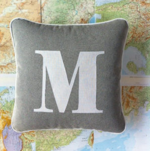 Piped cushion with appliquéd M